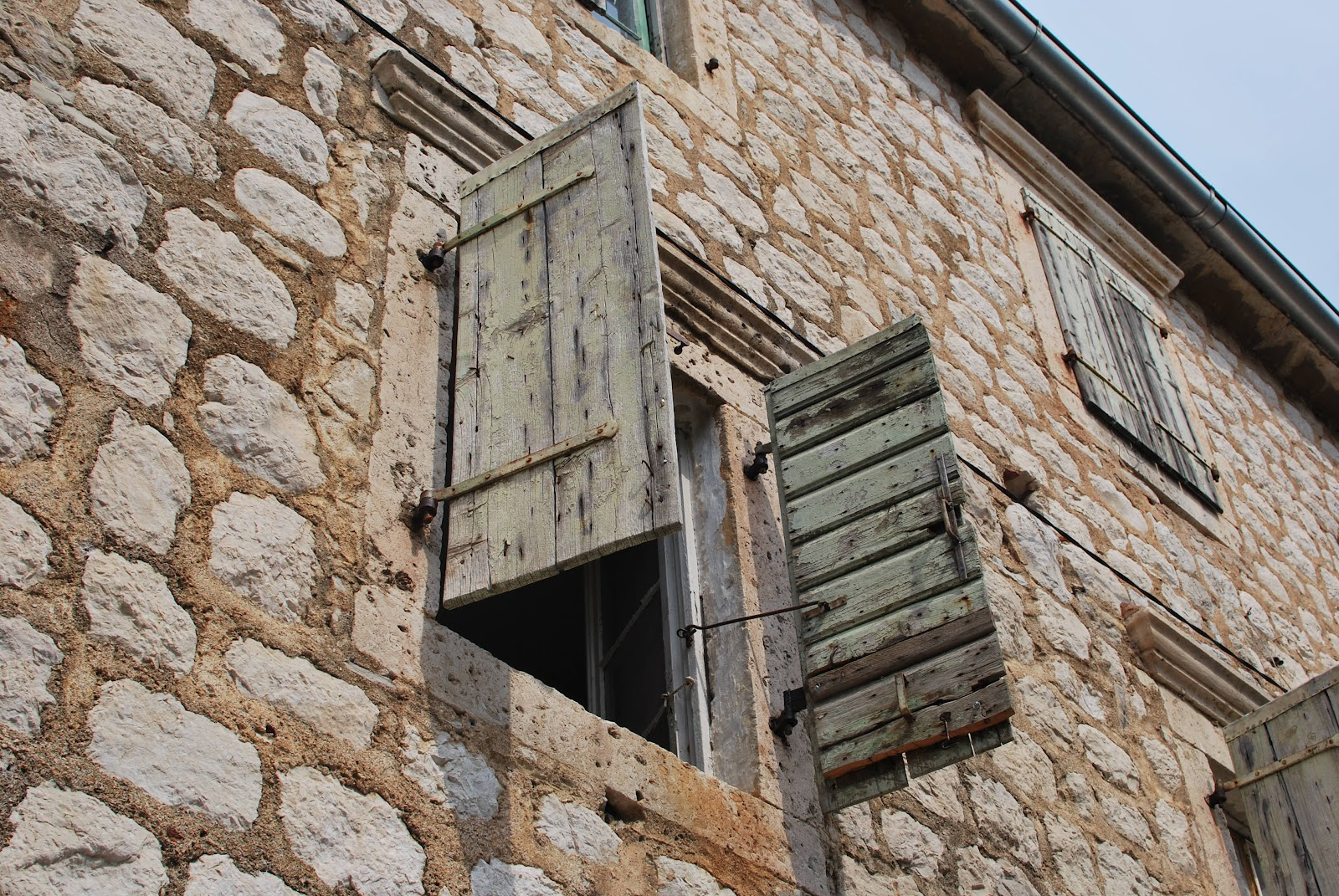 A closer look at the stone architecture and weathered shutters common in this region