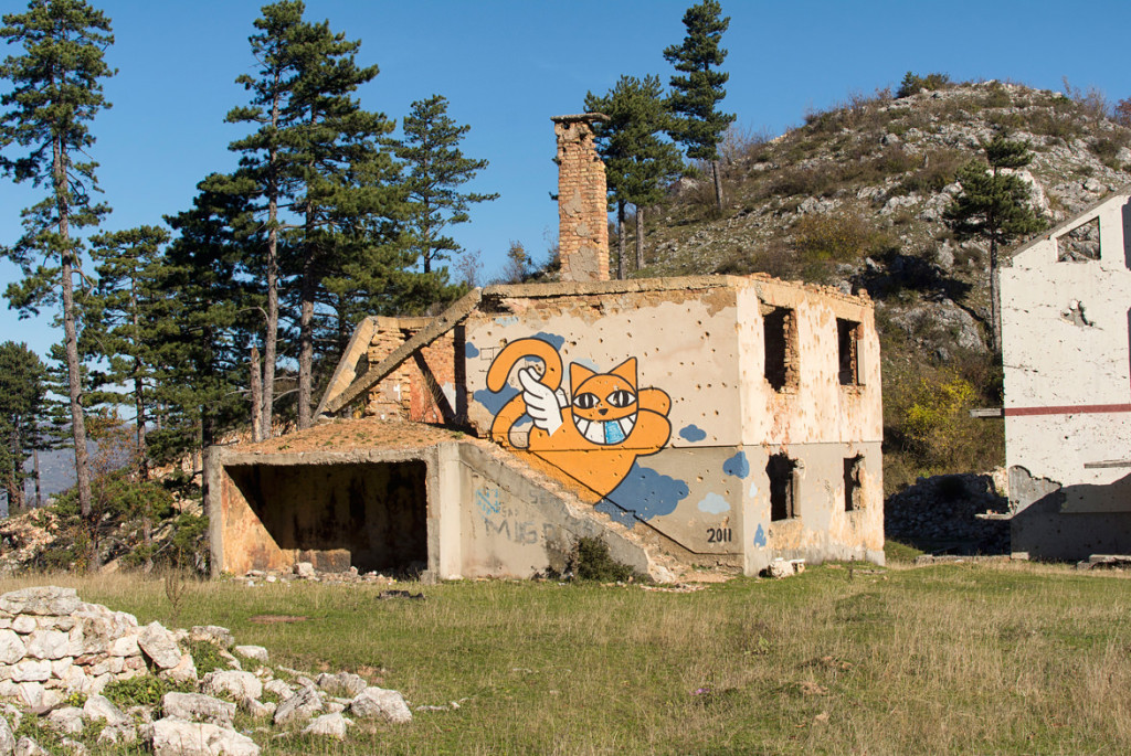 "An abandoned building nearby with a ""monsieur chat"" tag on it"