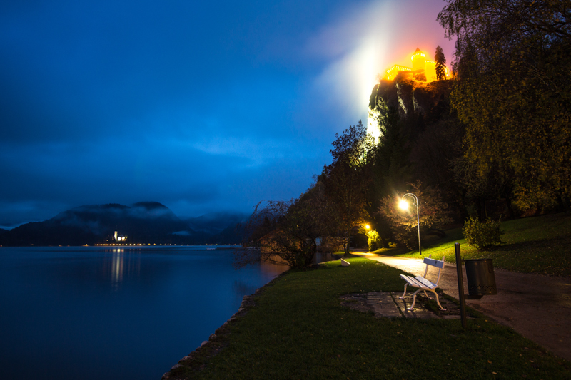 The photo shows Bled, Slovenia on a very misty evening. The lit up castle gives off this crazy glow that makes it look like straight out of some neon fairytale